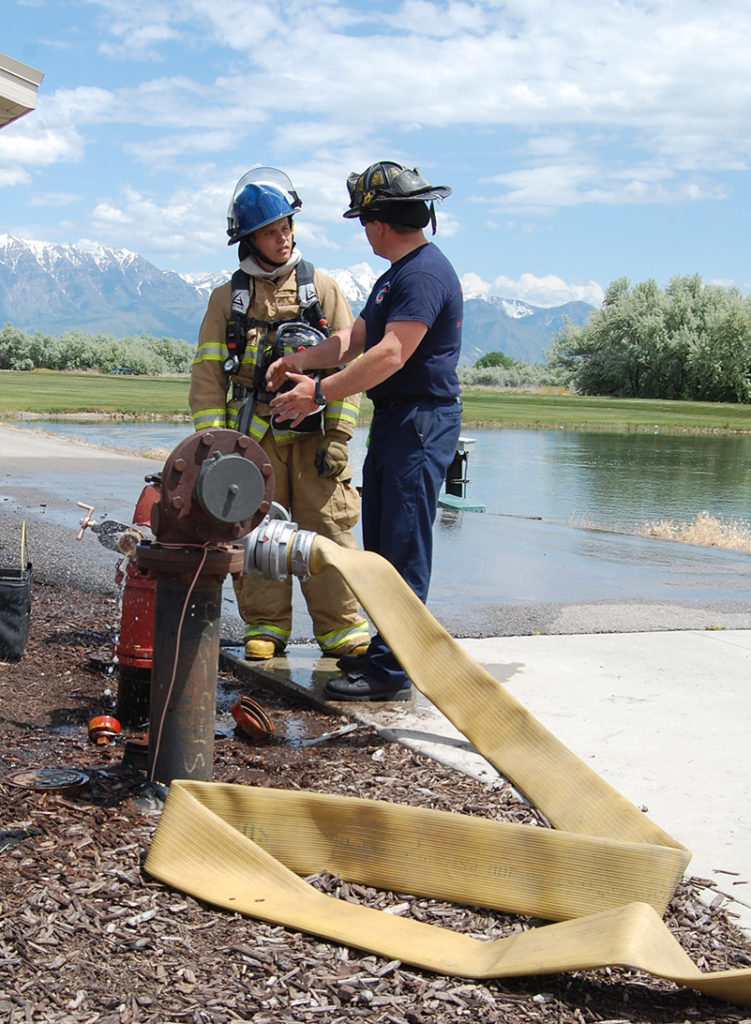 10-year Lehi Firefighter Tee Hover (right) reviews the results and details of the training scenario with Intern Zac Lucero. Photo: Cavett Ishihara