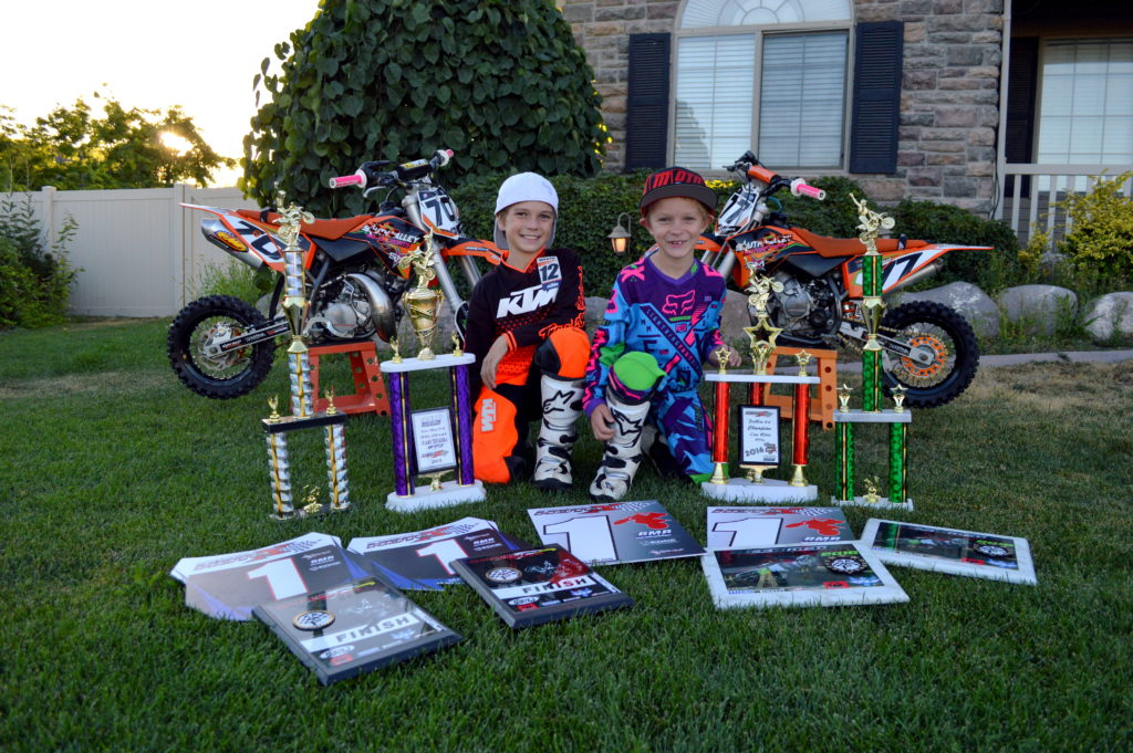 Jett and Cruz White surrounded by motocross racing awards. Photo courtesy of the White family