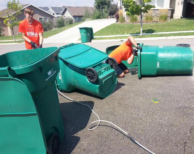 Skyridge Football cleans garbage cans to raise money for Shelbie. Photo courtesy of Greg Adamson